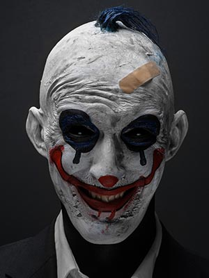 Terrible clown and Halloween theme: Crazy terrible blue clown in black suit isolated on a dark background