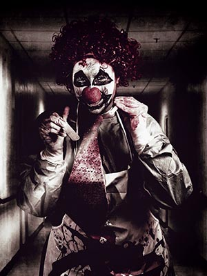Madness the creepy medical clown standing in grunge hospital hallway with flashlight and tongue prong. Terminal treatment